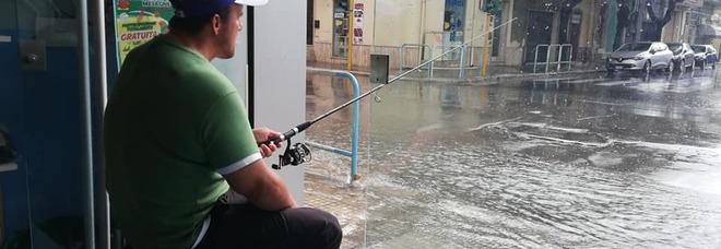 """L'attore Antonio Mitrugno che inscena una """"pesca"""" dopo il maltempo"""
