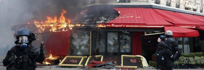 Gilet gialli, guerriglia a Parigi: palazzo in fiamme, negozi assaliti. Castaner: «Assassini»