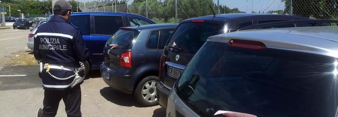 Un agente della polizia locale intento a multare le auto in sosta